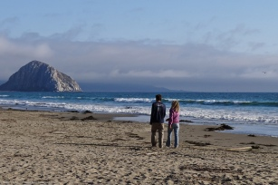 A young couple walk towards Morro Rock from North Morro Strand S